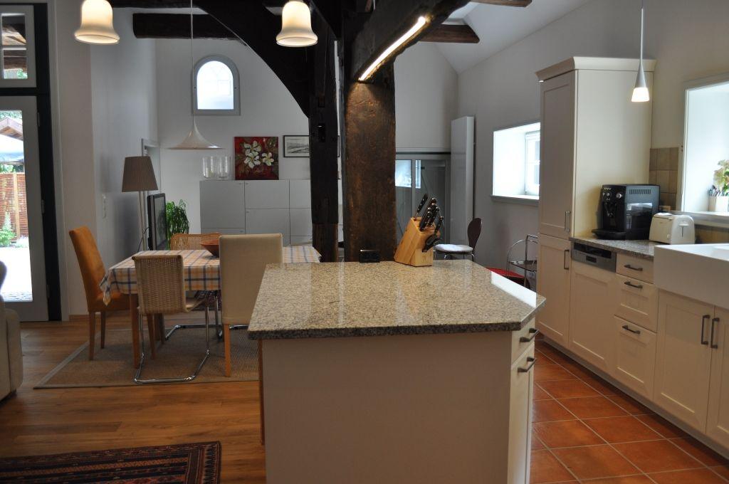 Gemütliches, helles Wohn-/Esszimmer mit offener Küche und sichtbarer Balkenkonstruktion
